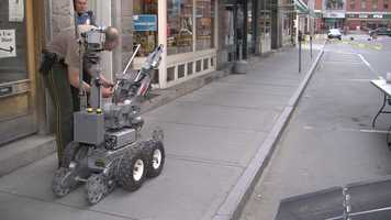 A bomb squad robot prepares to inspect the box.