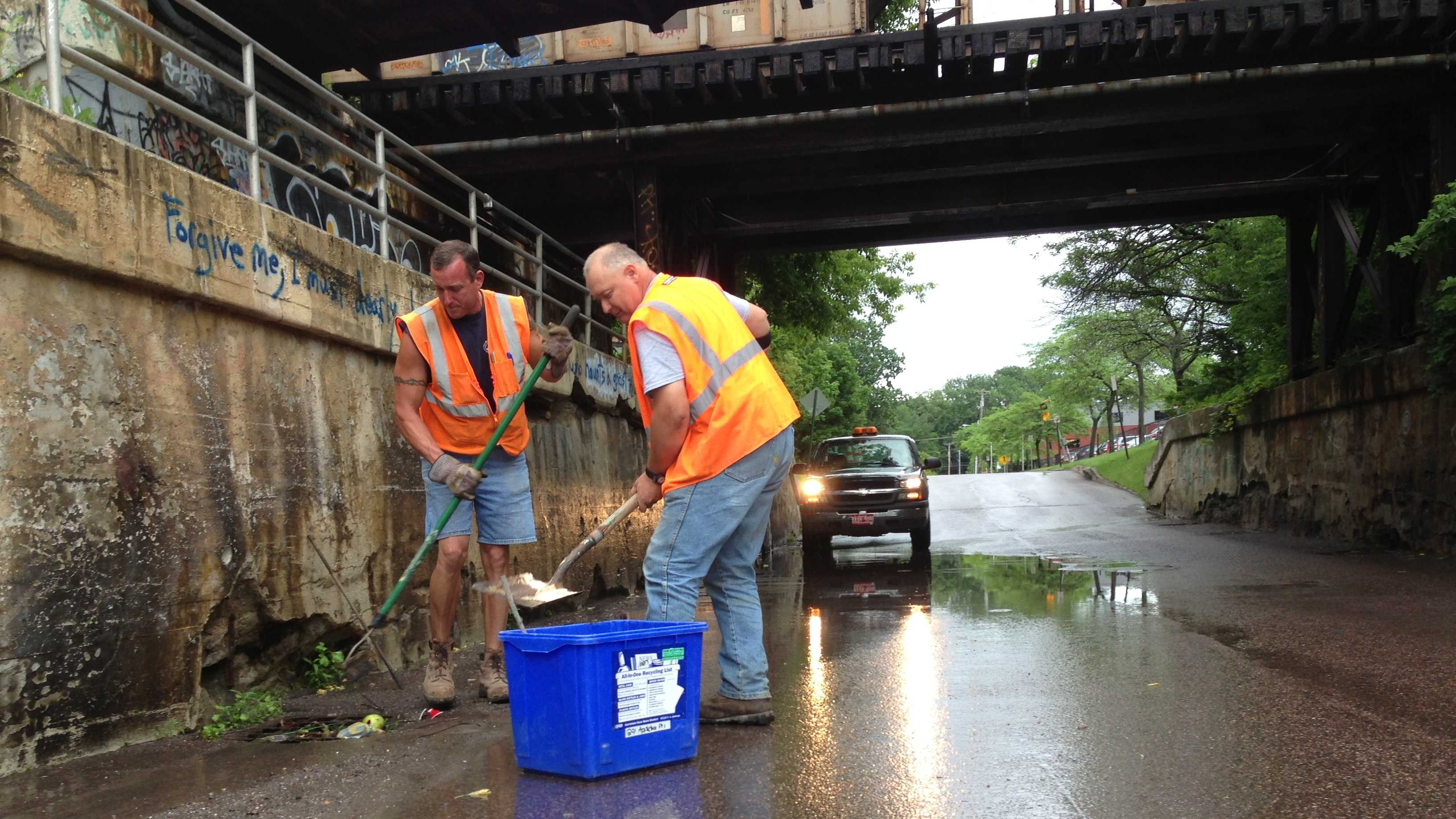 Department of Public Works crew members clean out catch basins clogged with debris.