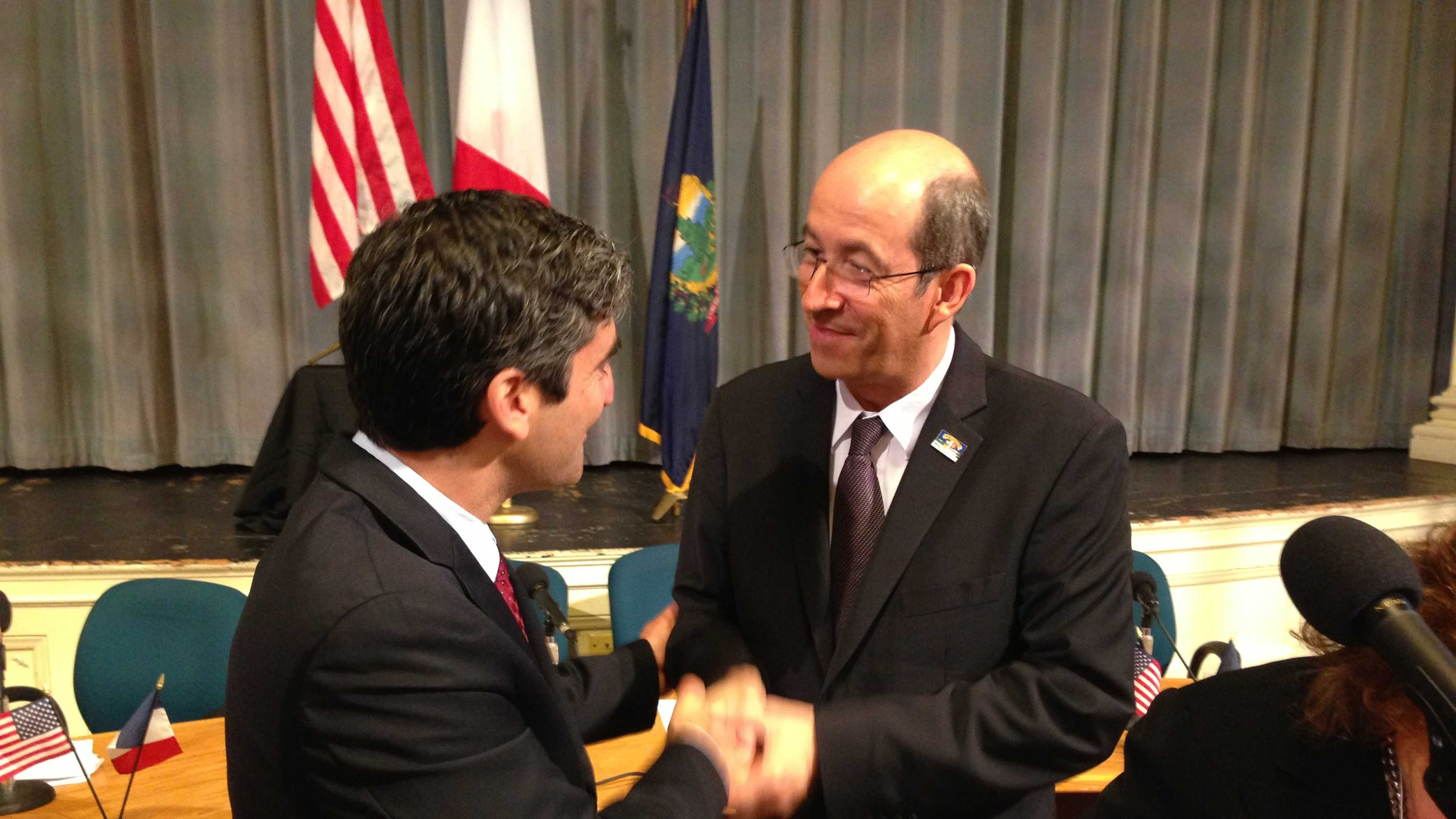 Burlington Mayor Miro Weinberger (L) shakes hands with Mayor Michel Lamarre of Honfleur, Normandy, France after signing a sister-city agreement.