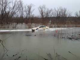 Car travels over a flood portion of Route 15 in Cambridge, Vt.