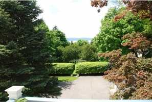 Deep landscaped lot with trees in front for privacy.