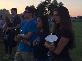 Holding candles and remembering Taoufik Maknani, 17, and Michael Lawson.