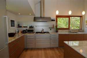 Poggenpohl kitchen featuring quartz countertops, Wolf range, sub-zero freezer & high-end fixtures opens to dining area & deck.
