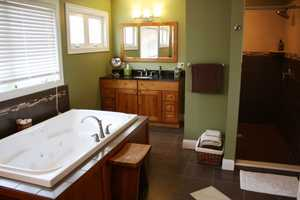 A master en-suite with dual sinks, a whirlpool tub, and a walk-in, tiled shower.
