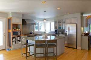 Kitchen has granite counters, douglas fir built-ins, oversized island, & new appliances including Blue Star range.