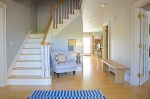 Foyer features hardwood floors, stairway and cool-complimentary colors.
