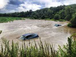 Two vehicles are seen in a flooded cornfield in Chester, Vt.