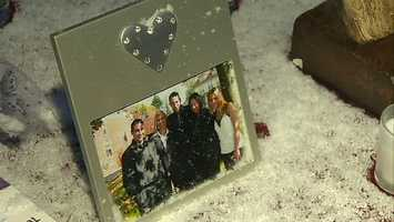 Friends and family held back tears and lit candles in a light snowfall.