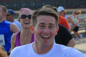Here's John Meyer smiling for the camera, with Janelle Hall in the background. John finished the half-marathon in 2:18:47.