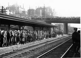 A large crowd at the railroad station in March 1942 bid farewell to young soldiers off to war.