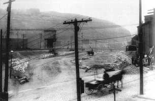 This April 1909 view shows a horse-drawn wagon near the intersection of Forward and Greenfield Avenues.  The Squirrel Hill Tunnel would later be constructed through the large hill in the background.