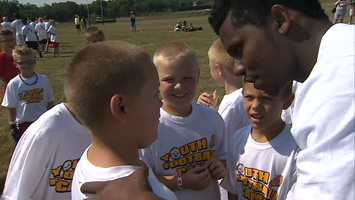 Baron Batch huddles with kids at the Steelers youth football camp.
