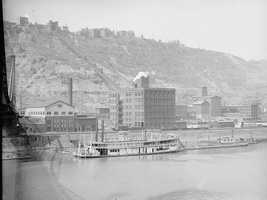 This is a look at Mount Washington sometime between the years 1900 and 1915. The photo was taken near the former Wabash Bridge. You can see the deforestation on the hill, and the smoke in the air.   Pictured in the distance is the Duquesne Incline.