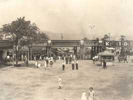 "Folks head toward Kiddieland and the ""Auto Race"" ride. The ride opened in 1930."