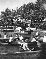 Folks enjoy rowboats on the lagoon on a sunny afternoon.