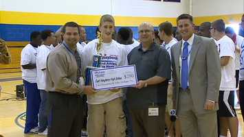 Kyle Whipple accepts a $250 check from Clearview Federal Credit Union on behalf of East Allegheny High School