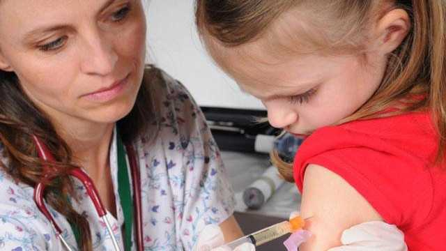 Child getting vaccine from doctor