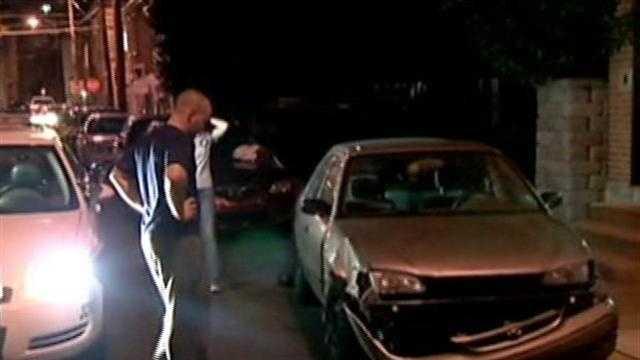 Eric Spielman looking at damaged car