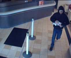 The robber is described as a man in his 20s or 30s, around 5 feet 9 inches or 5 feet 10 inches tall, with a thin to medium build, a beard/mustache, wearing a baseball cap under a hooded sweatshirt and jeans.