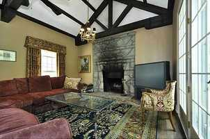 Family room features exposed wooden beams along the ceiling and is complimented by a dramatic stone fireplace.