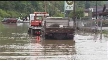 A city public works vehicle got stuck in flood waters on Streets Run Road and had to be pushed out by a tow truck.
