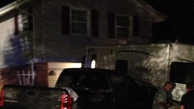 1 injured as truck knocks camper into house