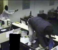 """According to police, """"One male vaulted the teller cage and retrieved cash from the teller drawers while the second male brandished a weapon."""""""