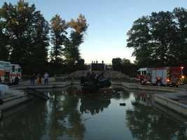 A car flipped over and landed on its roof in the fountain at the entrance to Highland Park on Thursday evening, and the way the vehicle came to rest may have been what ultimately saved the driver's life.