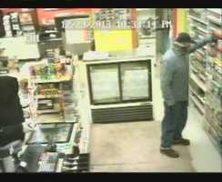 Surveillance video showed one man in a black hooded sweatshirt enter the store with a gun pointed at the clerk, followed by another man who pointed down and told the woman to get on the floor.