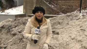 Amber Nicotra reports next to a mound of ice and snow on Woodlawn Avenue in Wilkinsburg.