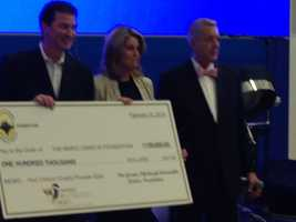 Mario and Nathalie Lemieux accept a check for $100,000 on behalf of the Mario Lemieux Foundation