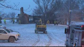 A backhoe was needed to demolish the house after a partial collapse made it too dangerous for firefighters to enter.