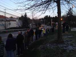 Murrysville residents line up along Old William Penn Highway to watch buses take students to Franklin Regional High School.