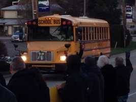Murrysville residents wave to students on a bus headed to Franklin Regional High School.