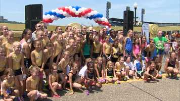 Gabby Douglas poses for a picture with girls from Pittsburgh gymnastics clubs after they set a world record for most simultaneous cartwheels on the Clemente Bridge.