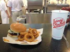 A burger with onion rings is ready to be served to a customer.