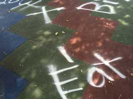 Profanity, racial slurs and vulgar language were spray painted on the rubber flooring and padding and the park benches at Charles F. Dinan Memorial Playground.