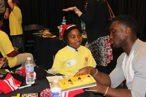 Josh Harris is showing his shopping buddy where he is in the 2014 Steelers yearbook, but 9-year-old Nisire isn't really sure that it's him!
