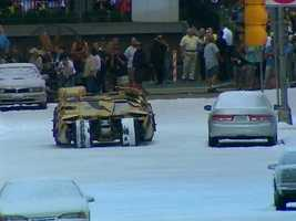 "A ""Tumbler"" Batmobile drives through the fake snow on downtown Pittsburgh streets."