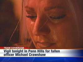 A tearful mourner at a candlelight vigil for Penn Hills police officer Michael Crawshaw, who was killed in the line of duty