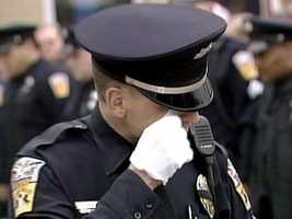 A police officer cries during the ceremonial final roll call for Michael Crawshaw in Penn Hills.