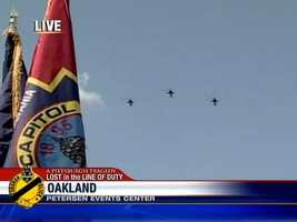 Three military helicopters pay tribute to the fallen officers.