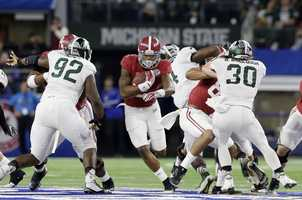 Alabama running back Derrick Henry takes the ball up field against Michigan State during the first half of the Cotton Bowl NCAA college football semifinal playoff game, Thursday, Dec. 31, 2015, in Arlington, Texas.
