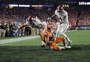 Clemson's Hunter Renfrow catches a touchdown pass in front of Alabama's Minkah Fitzpatrick and Eddie Jackson during the first half of the NCAA college football playoff championship game Monday, Jan. 11, 2016, in Glendale, Ariz.