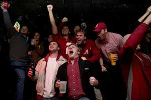 Alabama fans, Joe Kazoiw, center, 22, of Atlanta, Bruce Gurnowski, left, 21, of Newark, N.J., Zach Soto, back left, 21, of Hoover, Ala., and Mark Smith, back right, 22, of Indianapolis, Ind., cheer after a touchdown during the NCAA college playoff championship football game between Alabama and Clemson at at Gallettes Bar on, Monday, Jan. 11, 2016, in Tuscaloosa, Ala.