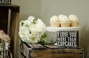 """This cool """"I love you more than cupcakes"""" can be a neat sign to show the desserts names and/or show the whimpsy in the couples fun selections. Great """"Country/Western"""" themed wedding setup. (WinMock Bridal Show)"""