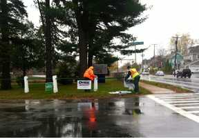 Monday morning in Nashua, N.H., workers remove campaign signs.
