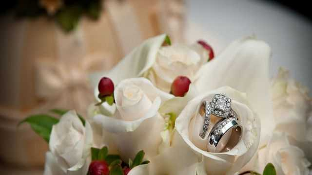 The photographer shows off the wedding band and ring in this beautiful white bouquet with red berries that looks like a wonderful Christmas themed wedding shot.