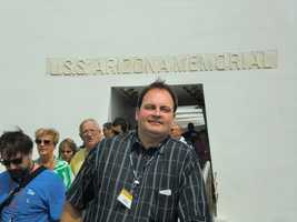 Austin in front of the U.S.S. Arizona Memorial sign with several other visitors.