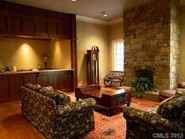 Basement Den with fireplace and bar
